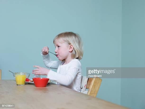 4-5 year old sits eating breakfast