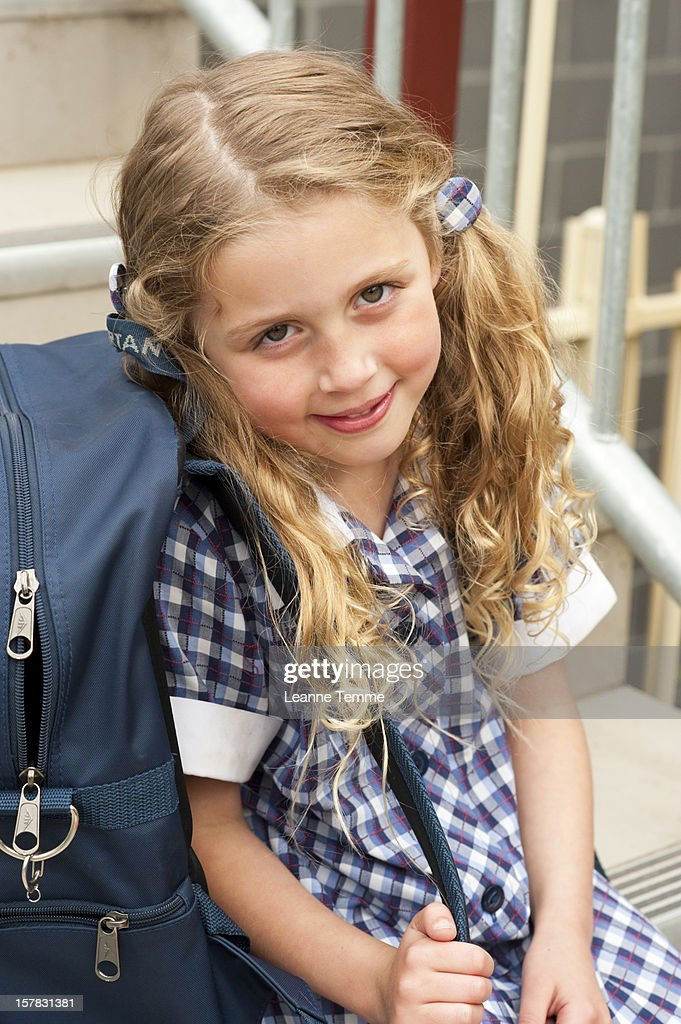 6 year old sitting on steps after school : Stock Photo