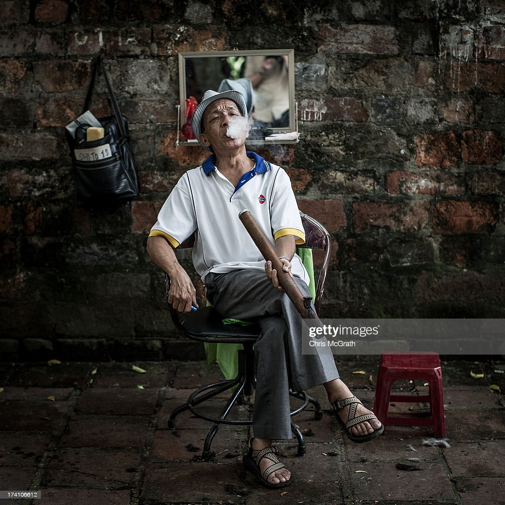 78 year old street barber Mr Thuan, smokes a pipe as he waits for customers at his roadside barber shop on July 20, 2013 in Hanoi, Vietnam. Mr Thaun has been a street barber for over 30 years after serving in the Vietnamese military. Hanoi's street barbers are a tradition that stretches back to the 18th century. On average a haircut will cost between 1 and 4 USD depending on the fame of the barber and if you are a regular or not. Many of the barbers are ex-miltary personel, retired from service and looking to keep busy or to help cover weekly expenses for their families.