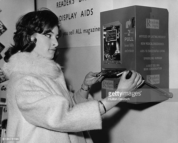 18 year old Suzanne Franks buys a Reader's Digest magazine from a vending machine at the Newsagents' Fair at Olympia | Location Empire Hall Olympia...