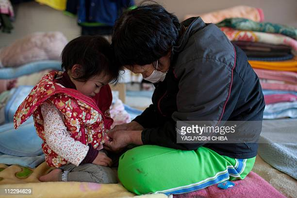 70 year old tsunami survivor Chiiko Nakanome takes care of her 2 year old granddaughter Ena at an evacuation centre in Rikuzentakata city Iwate...