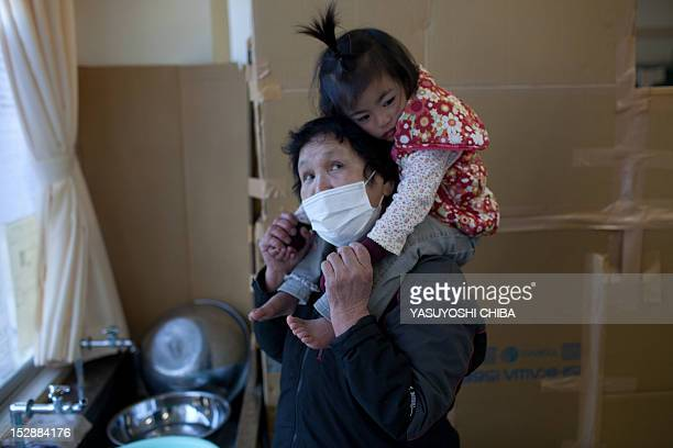 70 year old tsunami survivor Chiiko Nakanome takes care of her two year old granddaughter Ena at an evacuation centre in Rikuzentakata city Iwate...