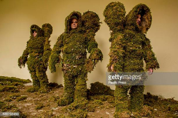 31 year old Vanesa Diaz 55 year old Juan Carlos Andres and 32 year old Fernando Arroyo Dominguez stand fully dressed as moss men before the Corpus...