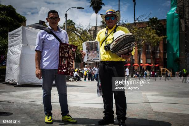 34 year old Venezuelan lawyer Carlos Gutierrez and 36 year old Venezuelan lawyer Daniel Marcano pose for a photo as they sell souvenirs hats and...