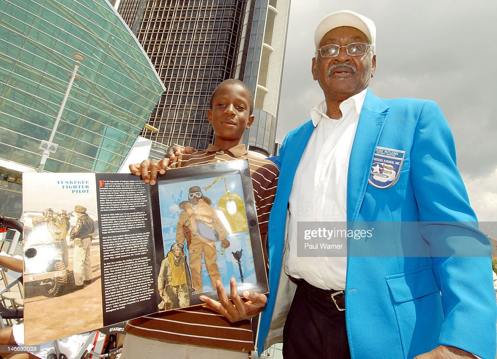 10 year old Warren Galloway (L) of Grosse Pointe Park, MI poses with his rare GI Joe Tuskegee Airman action figure and Tuskegee Airman Jesse Rutledge at the opening ceremony for the 2012 Detroit River Days Festival at the Detroit RiverWalk on June 22, 2012 in Detroit, Michigan.