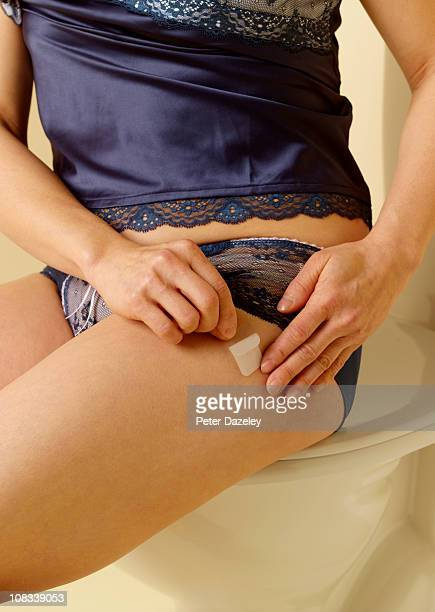 49 year old woman applying HRT patch