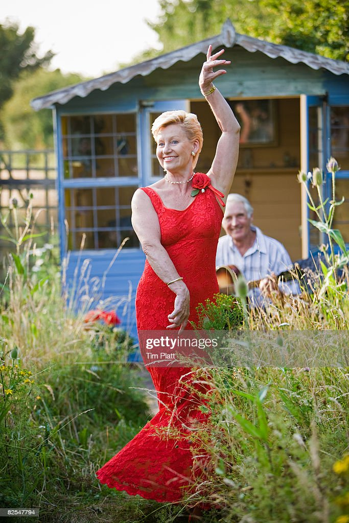 63 year old woman dancing in garden : Stock Photo