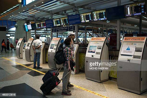 Year2014aviationaccidentsafetyFOCUS BY Dan Martin This photo taken on December 11 shows tourists looking at the information screens at Kuala Lumpur...