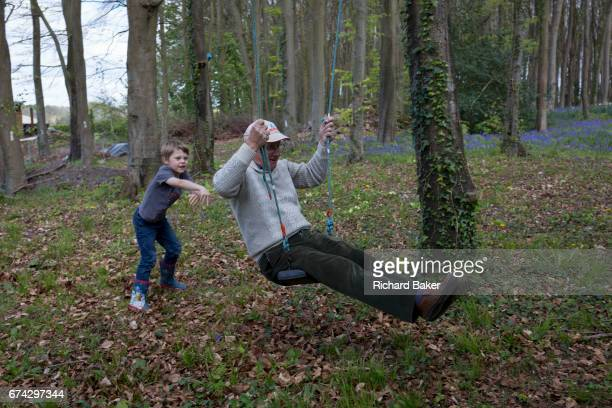 A 7 yearold boy pushes his 75 yearold granddad on a swing in local woods on 23rd April 2017 in Wrington North Somerset England