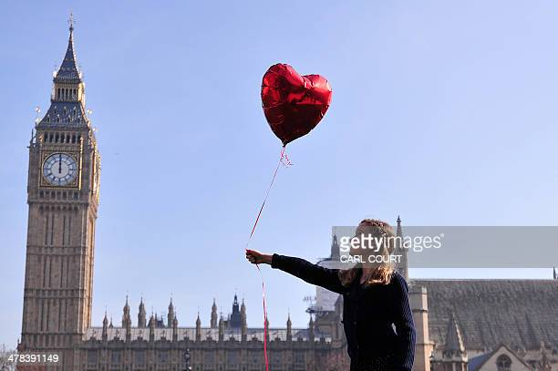 9 yearold Mili Baxter releases a red balloon in front of the Houses of Parliamnent in central London on March 13 2014 in a recreation of British...