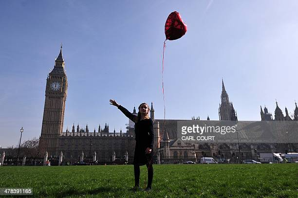 9 yearold Mili Baxter releases a red balloon in front of the Houses of Parliament in central London on March 13 2014 in a recreation of British...