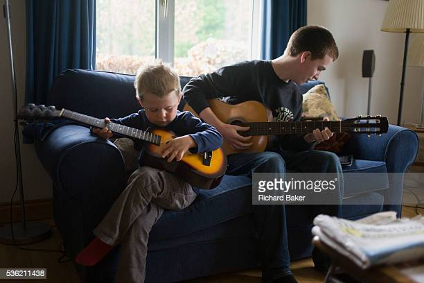 A 16 yearold teenager and his 4 yearold cousin sit on a sofa to play acoustic guitar together in the family living room Playing their musical...