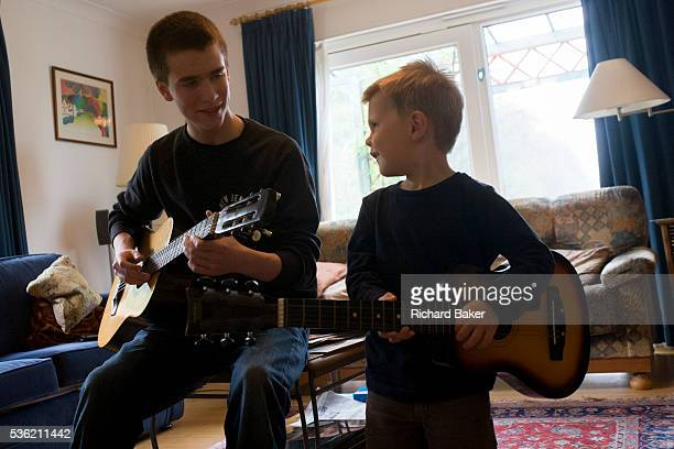 A 16 yearold teenager and his 4 yearold cousin smile at each other while playing acoustic guitar together in the family living room Playing their...