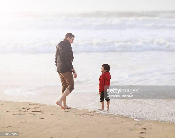 A 5 years old boy and his dad on the beach