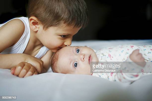 A 4 years old boy kissing his baby sister