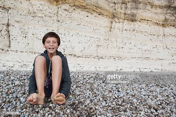 12 years old boy laughing and sitting on a beach