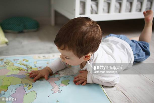 A 2 years old boy looking at a map