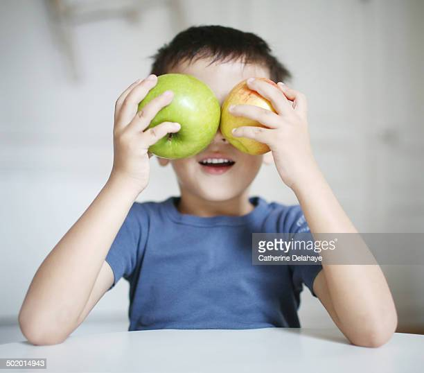 A 5 years old boy playing with apples