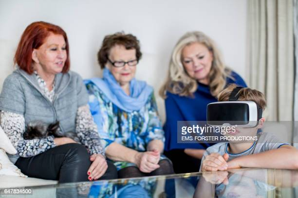 9 years old boy teaches grand mother and great grandmother and Bestager woman how to use VR glasses - media searches