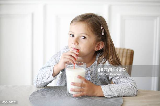 A 5 years old girl drinking milk