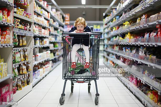 A 3 years old girl in a shopping cart
