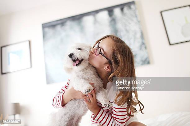 A 10 years old girl kissing her dog