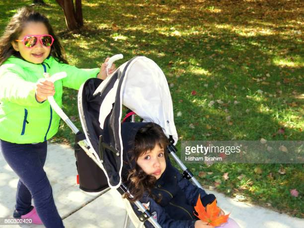 5 years old girl pushing her little 3 years old sister in a stroller.