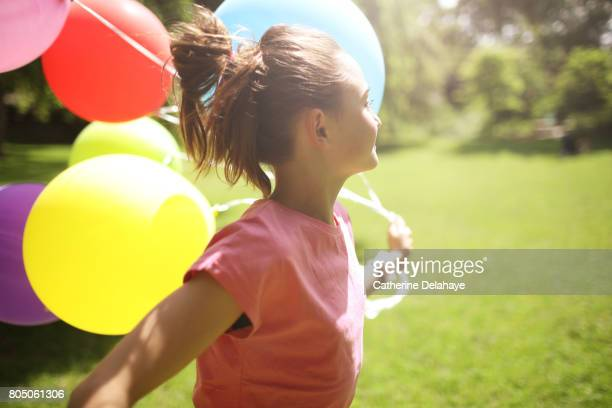 A 10 years old girl running with balloons in a park