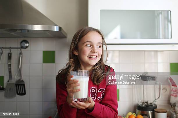 A 10 years old girl with a glass of milk