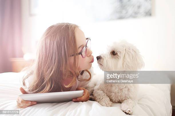 A 10 years old girl with her dog and a tablet