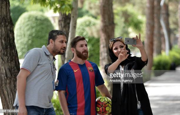 25 years old Iranian Lionel Messi lookalike university student Reza Parastesh poses for a photo with people in Tehran Iran on May 11 2017 Reza grew a...
