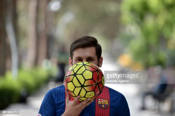 25 years old Iranian Lionel Messi lookalike university student Reza Parastesh poses for a photo while holding a soccer ball in Tehran Iran on May 11...