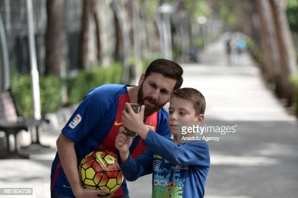25 years old Iranian Lionel Messi lookalike university student Reza Parastesh poses for a photo with a kid while holding a soccer ball in Tehran Iran...