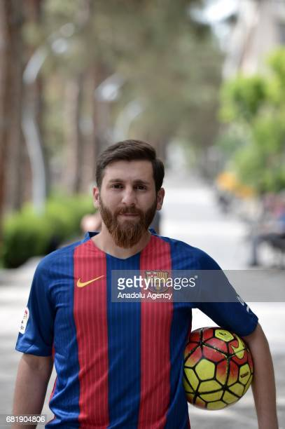 25 years old Iranian Lionel Messi lookalike university student Reza Parastesh poses for a photo with a soccer ball in Tehran Iran on May 11 2017 Reza...