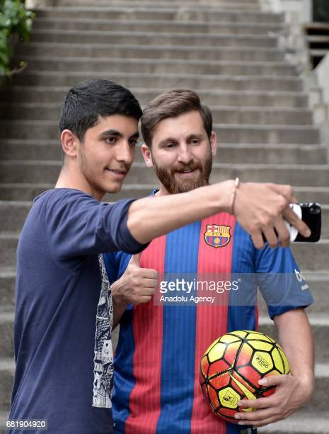 25 years old Iranian Lionel Messi lookalike university student Reza Parastesh poses for a photo with a young fan in Tehran Iran on May 11 2017 Reza...