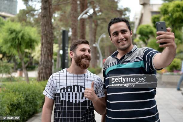 25 years old Iranian Lionel Messi lookalike university student Reza Parastesh poses for a photo with a fan in Tehran Iran on May 11 2017 Reza grew a...