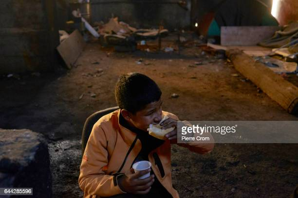 12 years old Laqad from Afghanistan takes a bite of bread on February 23 2017 in Belgrade Serbia The unaccompanied child lives since 6 months in an...