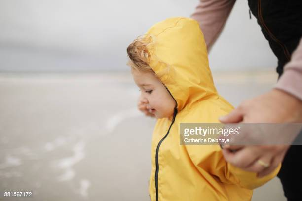A 2 years old little girl wearing a oilkin on the beach