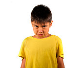 8 years old male child sad and ashamed after suffering reprimand isolated on white background wearing yellow t-shirt in emotional kid scolded and nagged face expression