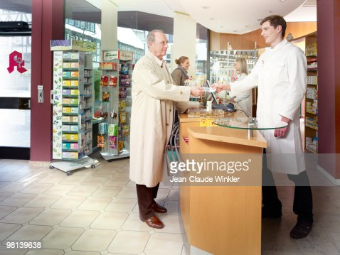 70 years old male paying in pharmacy : Stock Photo