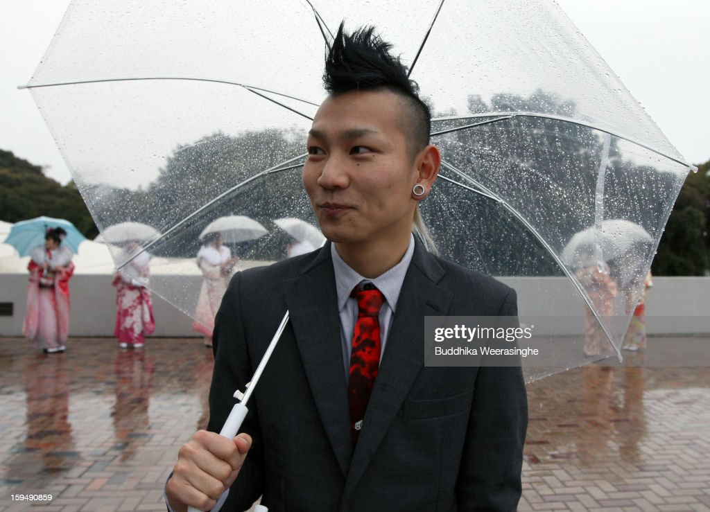 20 years old man stands in the rain during the 'Coming-of-Age Day' celebration at Cultural Hall on January 14, 2013 in Himeji, Japan. The event involves 20-year-old Japanese people celebrating their eligibility to drink alcohol, smoke and vote.