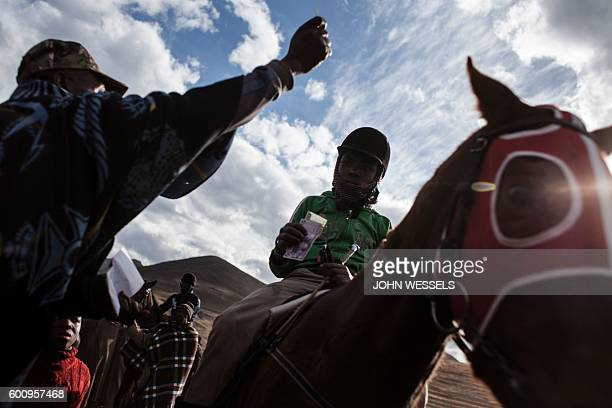 16 years old Mosotho jockey Mokikeng Tladi receives a reward after the race on July 15 2016 in Semonkong Horseracing in the mountain kingdom of...