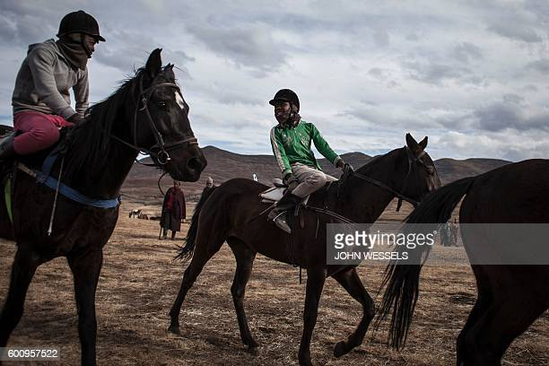 16 years old Mosotho jockey Mokikeng Tladi talks with fellow jockeys prior to their race on July 16 2016 in Semonkong Horseracing in the mountain...