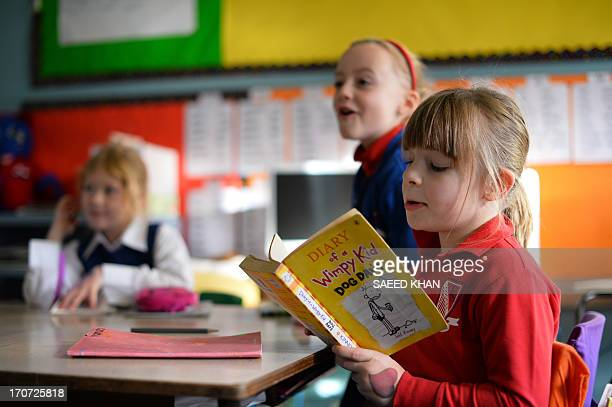 WORLD 6 years old student Frances McMillan reads a book inside a classroom at school in the Coogee suburb of Sydney on June 17 2013 AFP PHOTO / Saeed...