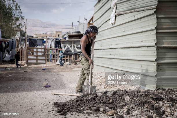 A 15 years old Syrian man is pictured while digging trenches for the basic sewage system that runs through the settlement