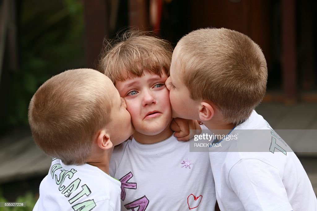 10 years old triplets Josef, Katerina And Daniel (L toR) hug each other during a meeting of twins and multiples in Zvole, Czech Republic, south Moravia, on May 29, 2016 The biggest meeting of twins and multiples in the Czech Republic was today in Zvole, 40 km east of Brno. Meeting attended by one hundred pairs, take a family photo. This is a unique event in the Czech Republic. / AFP / RADEK
