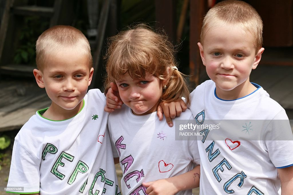 10 years old triplets Josef, Katerina And Daniel (L toR) pose for a photo during a meeting of twins and multiples in Zvole, Czech Republic, south Moravia, on May 29, 2016. The biggest meeting of twins and multiples in the Czech Republic took place in Zvole, 40 km east of Brno. / AFP / RADEK