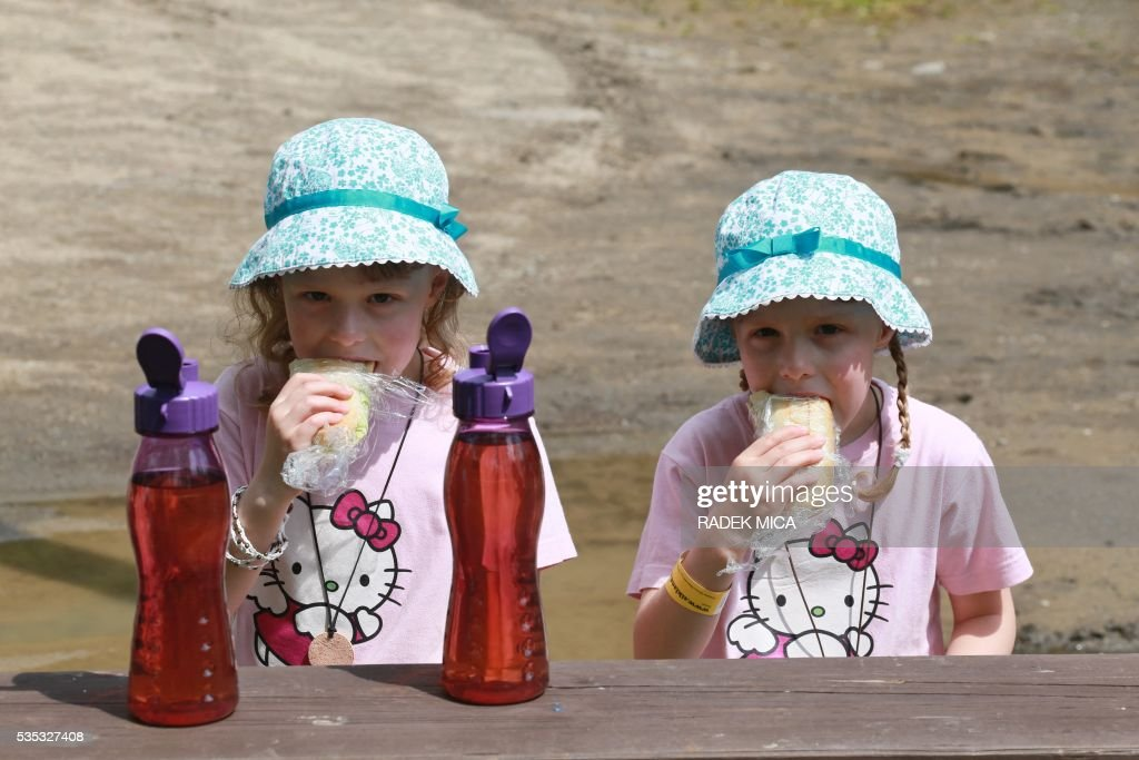 6 years old twins Ema (L) and Beta eat a sandwich during a meeting of twins and multiples in Zvole, Czech Republic, south Moravia, on May 29, 2016. The biggest meeting of twins and multiples in the Czech Republic took place in Zvole, 40 km east of Brno. / AFP / RADEK