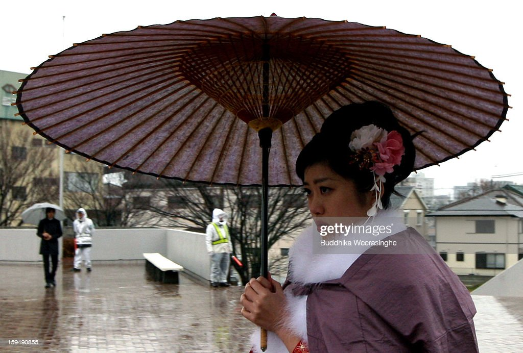 20 years old woman dressed in traditional kimono walks in the rain for her 'Coming-of-Age Day' celebration at Cultural Hall on January 14, 2013 in Himeji, Japan. The event involves 20-year-old Japanese people celebrating their eligibility to drink alcohol, smoke and vote.
