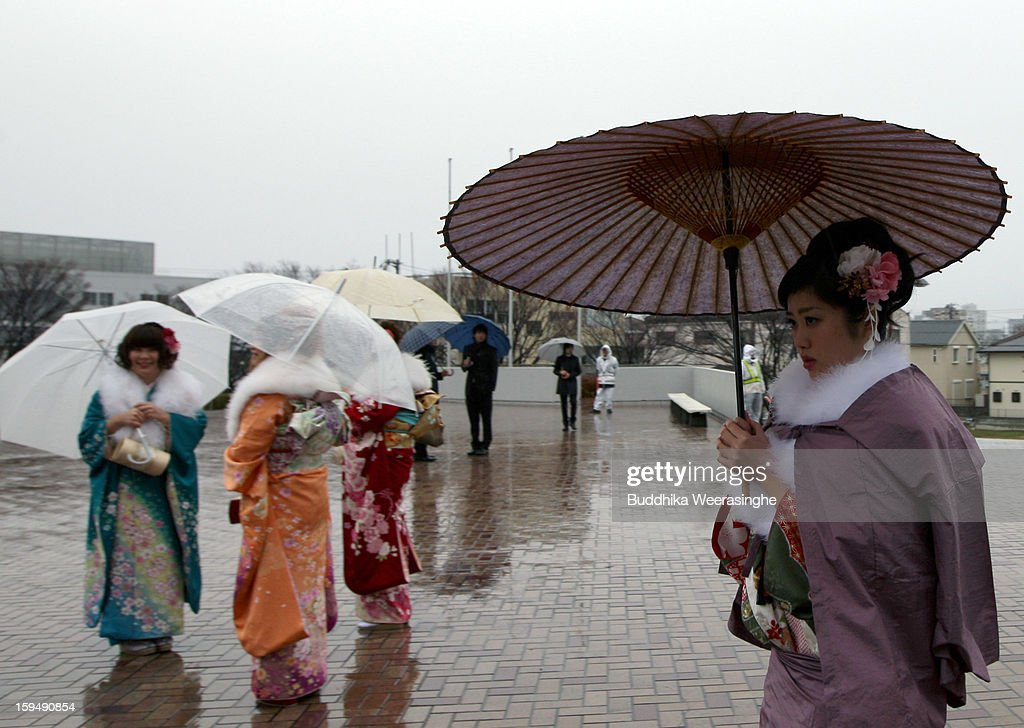 20 years old women dressed in traditional kimono walk in the rain for their 'Coming-of-Age Day' celebration at Cultural Hall on January 14, 2013 in Himeji, Japan. The event involves 20-year-old Japanese people celebrating their eligibility to drink alcohol, smoke and vote.